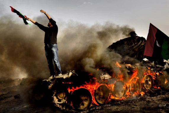 With the assistance of the international military coalition the rebels have now taken over the city of Ajdabiya. Shortly after the fall of Ajdabiya. Burned out tanks belonging to the Pro-Gardaffi forces destroyed by the international military coalition. Rebels fighters and locals are celebrating the victory. Man stands on a burning tank belonging to pro-Gardaffi forces.